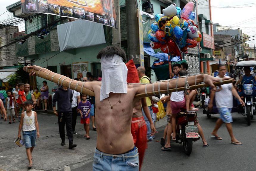 A penitent walks along a street towards a chapel as part of Lenten observance in Manila on April 2, 2015. -- PHOTO: AFP