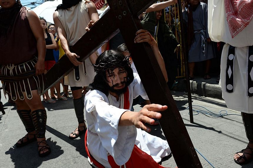 A man (centre), acting as Jesus, carries a wooden cross as residents re-enact the passion and death of Jesus as part of Lenten observance in Manila on April 2, 2015. -- PHOTO: AFP