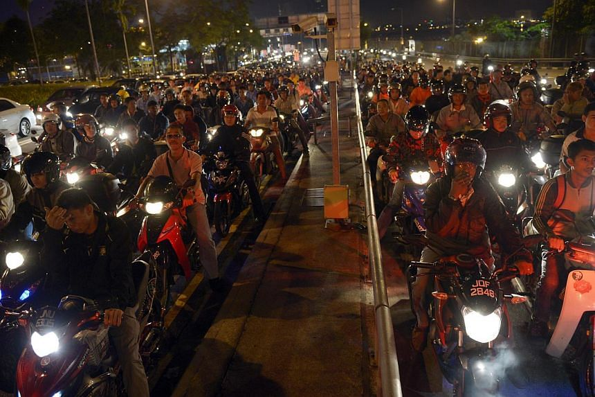 Long queues even at 5.30am as motorcyclists bound for Singapore wait for their turn at the Woodlands checkpoint. Under the tender for the two land checkpoints, at least 110 motorcycles should be cleared per hour per lane when all lanes are in operati