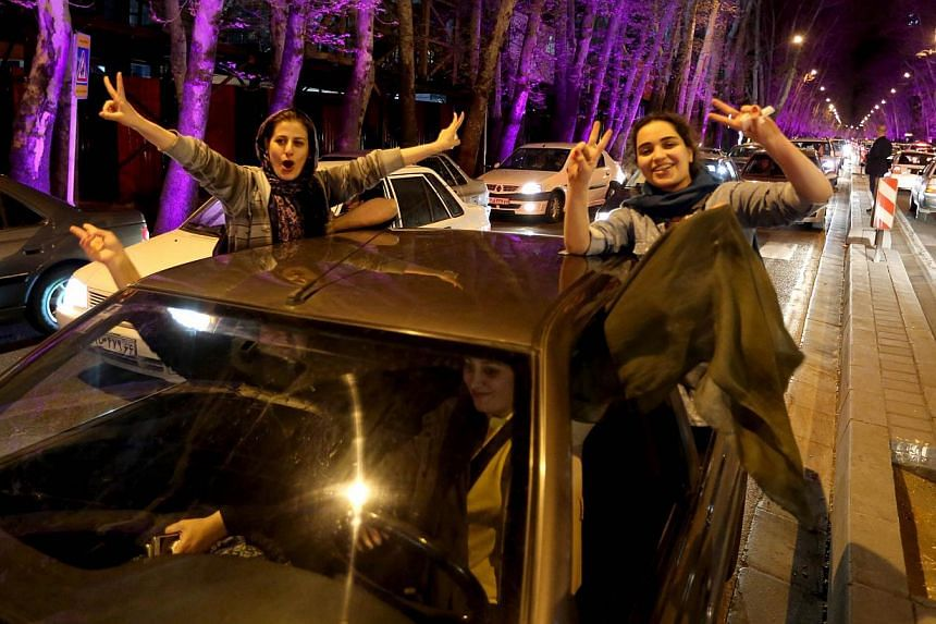 """Women sitting in a car flash the """"V for Victory"""" sign as they celebrateonVal-e-Asr Avenue in northern Teheran on April 2, 2015, after the announcement of an agreement on Iran nuclear talks.Hundreds of Iranians took to the streets in"""