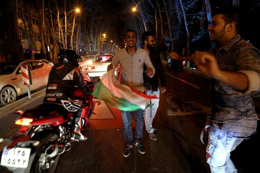 People dance and hold an Iranian flag as they celebrateonVal-e-Asr Avenue in northern Teheran on April 2, 2015, after the announcement of an agreement on Iran nuclear talks.Hundreds of Iranians took to the streets in Teheran early o