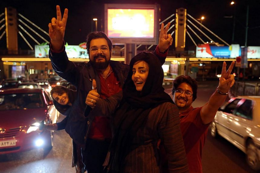 """People flash the """"V for Victory"""" sign as they celebrate onVal-e-Asr Avenue in northern Teheran on April 2, 2015, after the announcement of an agreement on Iran nuclear talks.Hundreds of Iranians took to the streets in Teheran early on Fri"""