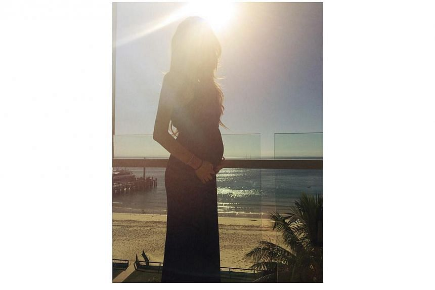 In another photo, a visibly pregnant Quinlivan is on her own on a balcony.-- PHOTO: FACEBOOK