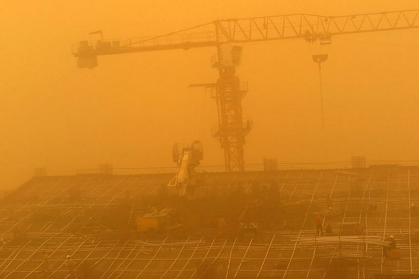 Construction workers are seen amid a sandstorm at one of construction sites in Dubai, United Arab Emirates, on April 2, 2015. Flights were disrupted, ships weighed anchor and schools were closed Thursday as a major sandstorm blew through Saudi A