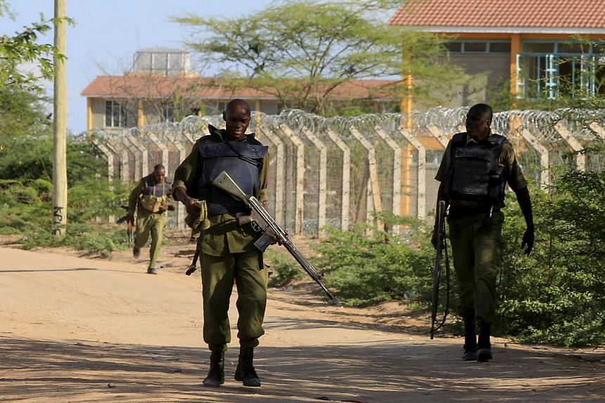 Kenya Defence Force soldiers walk near the perimeter wall where attackers were holed up at a campus in Garissa April 2, 2015.At least 147 students were massacred when Somalia's Shebab Islamist group attacked a Kenyan university on Thursday, t