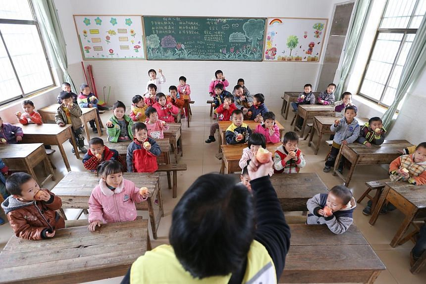 A volunteer giving out apples to kindergarten pupils at a school in China. -- PHOTO: ST FILE
