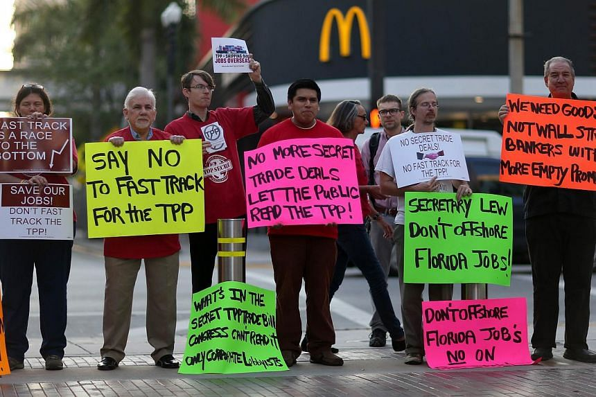 Protesters against the Trans-Pacific Partnership standing outside the Miami Dade College where the Greater Miami Chamber of Commerce was hosting US Treasury Secretary Jacob Lew on March 20, 2015. -- PHOTO: AFP