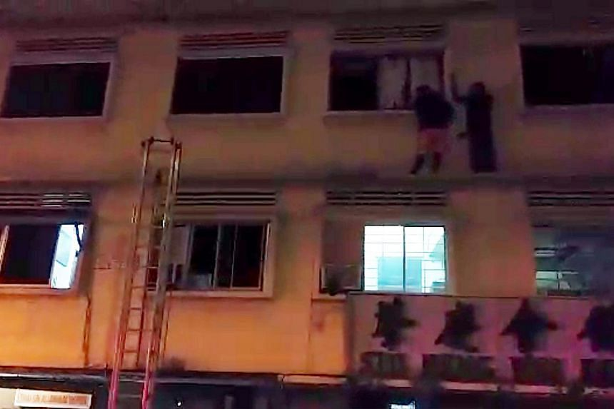 Two foreign workers who went out on the ledge on the third floor of the apartment in 35 Geylang Lorong 4 on December 7,2014, trying to get to safety from the fire that broke out on the ground floor. Four foreign workers died in the fire. -- PHOTO: SH