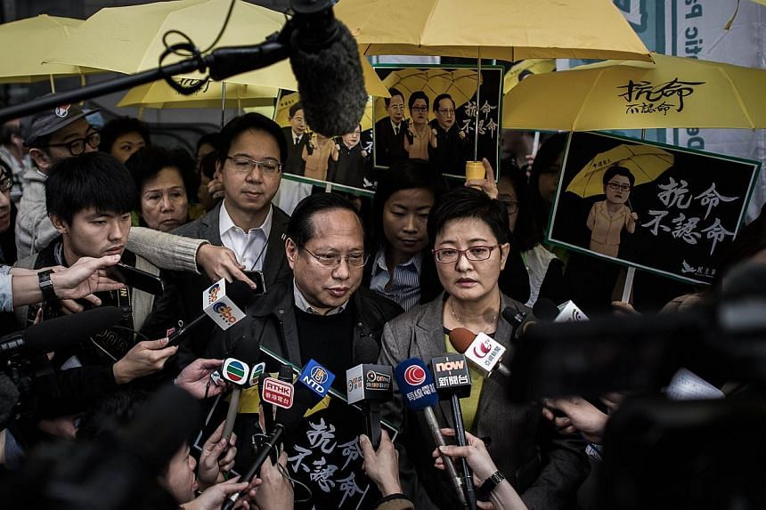 Albert Ho (centre, left) and Helena Wong (centre, right), both of the Democratic Party, speaking to the media outside the Wanchai police station in Hong Kong on March 2, 2015. -- PHOTO: AFP