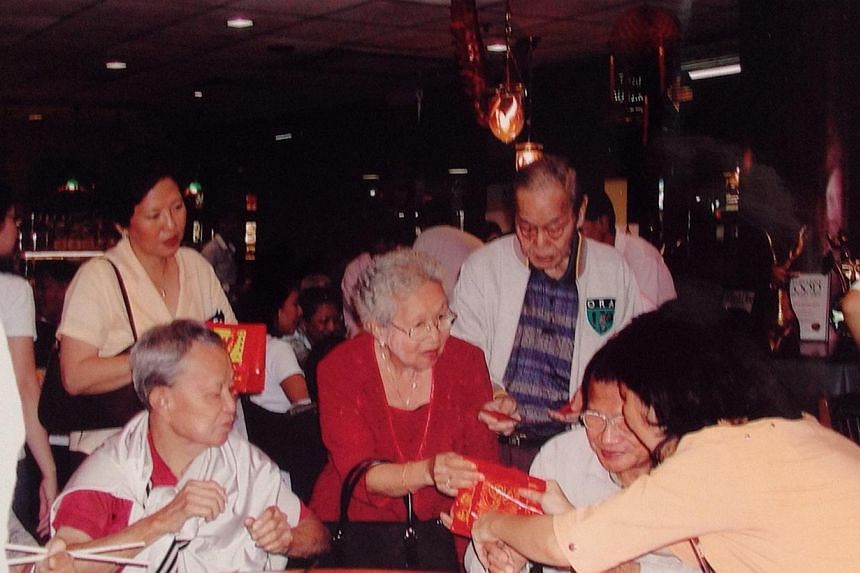 Mr Lim's mother Yeoh Sai Hoo (above, in red) and his late father Lim Ah Tee (in a sports jacket) giving Chinese New Year hongbao to leprosy patients in 2006, at a lunch that they hosted annually.