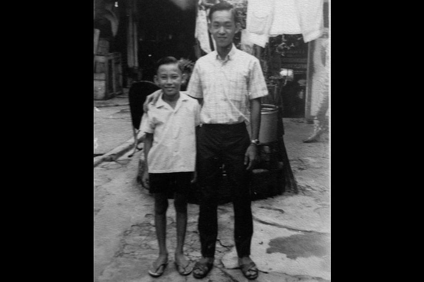 Mr Lim's mother Yeoh Sai Hoo (above, in red) and his late father Lim Ah Tee (in a sports jacket) giving Chinese New Year hongbao to leprosy patients in 2006, at a lunch that they hosted annually. At right, Mr Lim (right) in 1964 with a neighbour in t