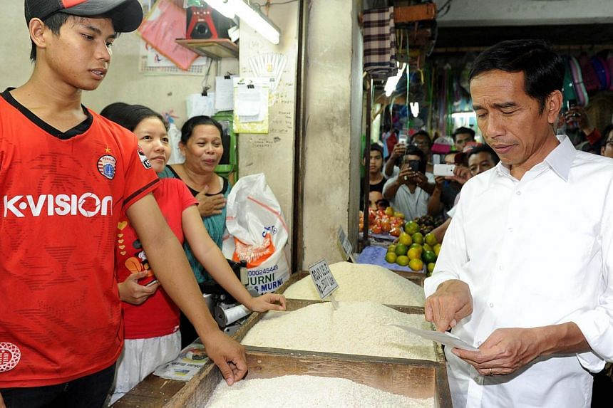 Mr Joko Widodo (right) visiting a traditional food market in Jakarta. With a slowing economy, the Indonesian President needs to attract investments. But to do that, he must address bureaucratic bottlenecks, reform the civil service, broaden the inves