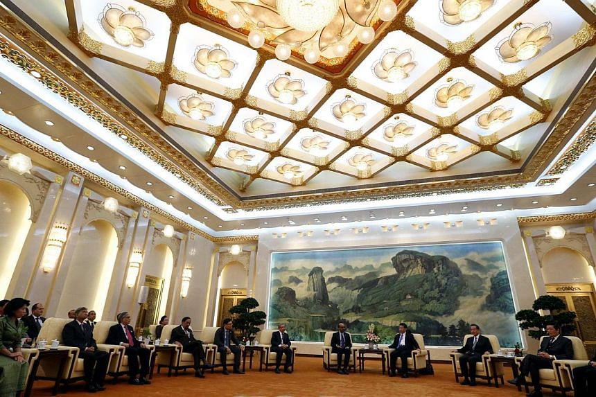 China's President Xi Jinping (fourth from right) meets with the guests at the Asian Infrastructure Investment Bank (AIIB) launch ceremony at the Great Hall of the People in Beijing in this Oct 24, 2014 file photograph. -- PHOTO: REUTERS