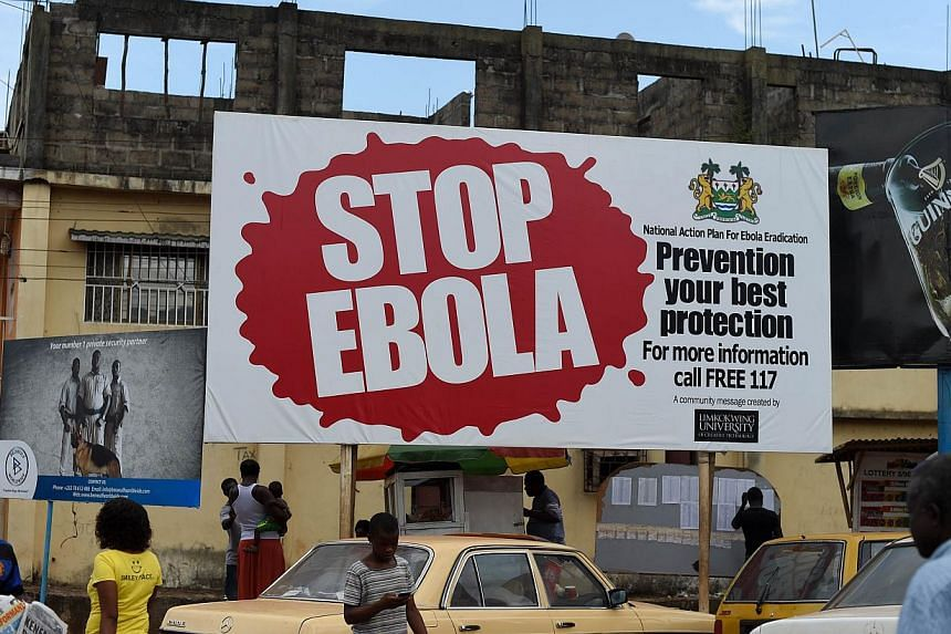 A picture taken on Nov 7, 2014, shows people walking past a billboard with a message about ebola in Freetown, Sierra Leone. -- PHOTO: AFP
