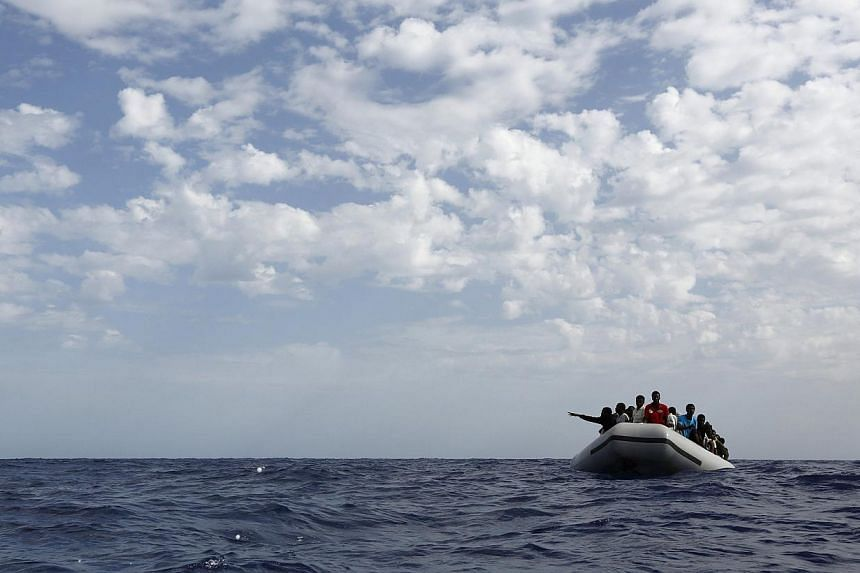 A group of 106 sub-Saharan Africans on board a rubber dinghy wait to be rescued by the NGO Migrant Offshore Aid Station some 25 miles off the Libyan coast, in this Oct 4, 2014 file photo. -- PHOTO: REUTERS