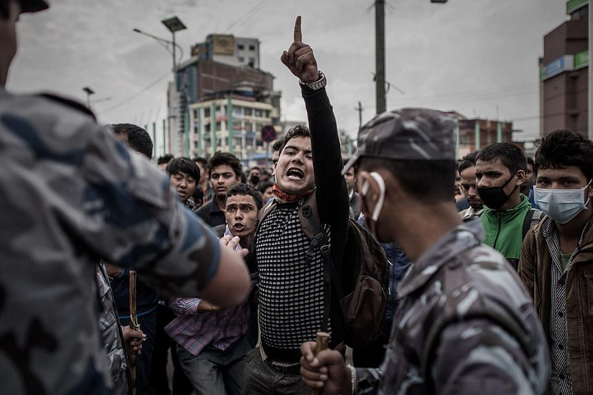 Riot police officers maintaining law and order on a street in Kathmandu yesterday as earthquake survivors desperate to leave the Nepalese capital showed their anger after promised special bus services failed to materialise.