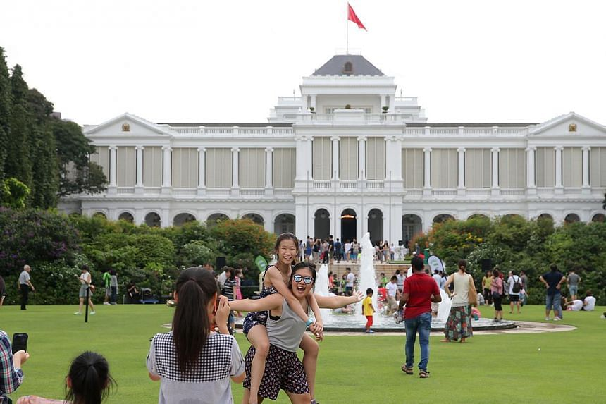 People taking photographs against the Istana on May 1, 2015. -- ST PHOTO: ONG WEE JIN