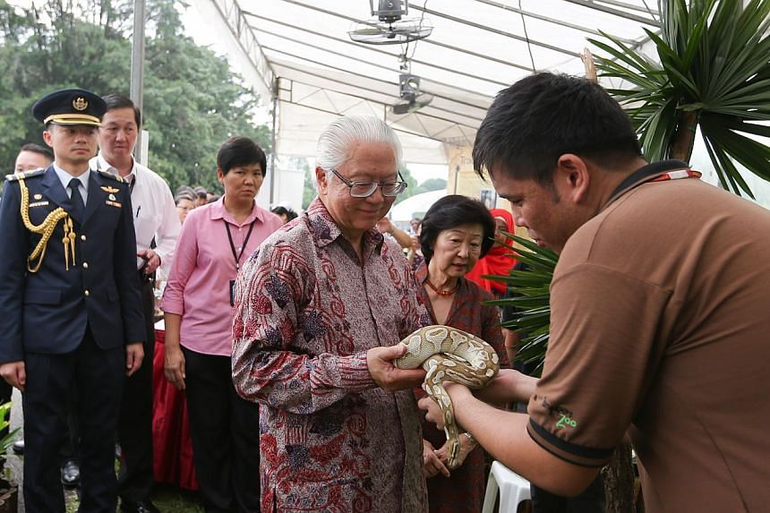 President Tony Tan holding a snake at the open house on May 1, 2015. With him is his wife, Mrs Mary Tan. -- ST PHOTO: ONG WEE JIN