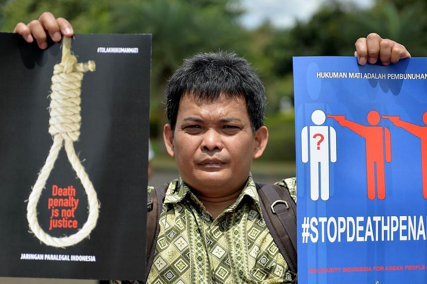 """A protester holding up a placard that reads """"'death row is a murder and death penalty is not justice"""" during an anti-death penalty rally in front of the palace in Jakarta on April 28, 2015. -- PHOTO: AFP"""