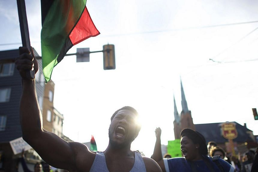 Mr Durmel Coleman, 23, marching as the flag bearer joining protestors to demonstrate over the death of Freddy Gray on April 30, 2015, in Philadelphia, Pennsylvania. -- PHOTO: AFP