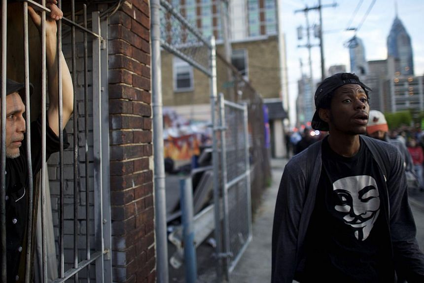 Mr William Sanders, 41, (left) a chef at Westey Tavern, observing protestors marching in demonstration over the death of Freddy Gray on April 30, 2015, in Philadelphia, Pennsylvania. -- PHOTO: AFP