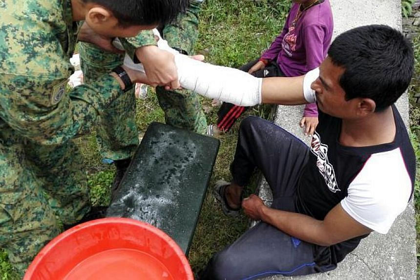 The SAF medical team stationed at the courtyard of a 1,500-year-old Hindu temple in Gokarna, a town on the outskirts of Kathmandu, apply plaster-of-paris on Mr Tirtha Lal Shrestha, a 31-year-old labourer who injured his wrist during the 7.8 magnitude