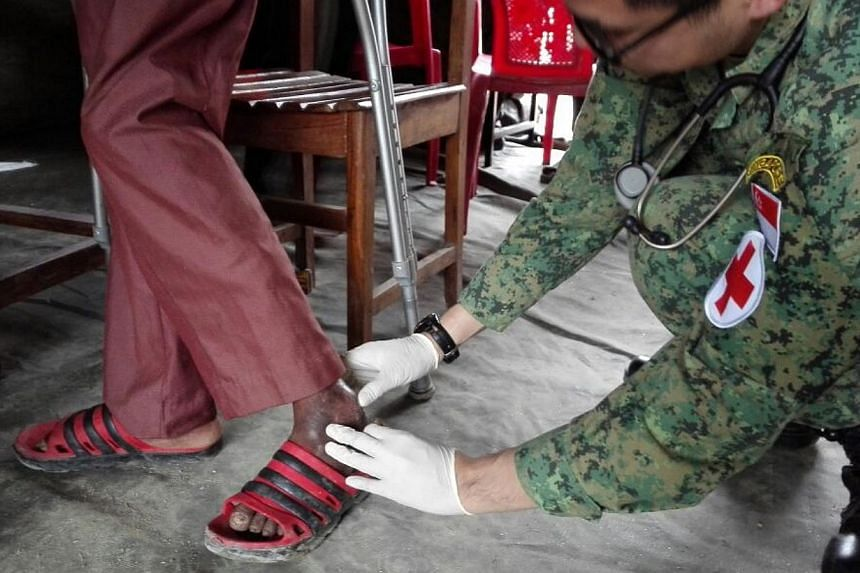 Major (Dr) Kok Wai Leong cleans Mr Lal Bahadur Bayarkoti's ankle injury at the SAF mobile clinic at the courtyard of a 1,500-year-old Hindu temple in Gokarna, a town on the outskirts of Kathmandu.--ST PHOTO: LIM YAN LIANG