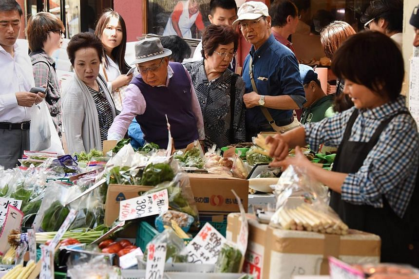 Shoppers choosing vegetables at a fruit and vegetable store in Tokyo on May 1, 2015. -- PHOTO: AFP