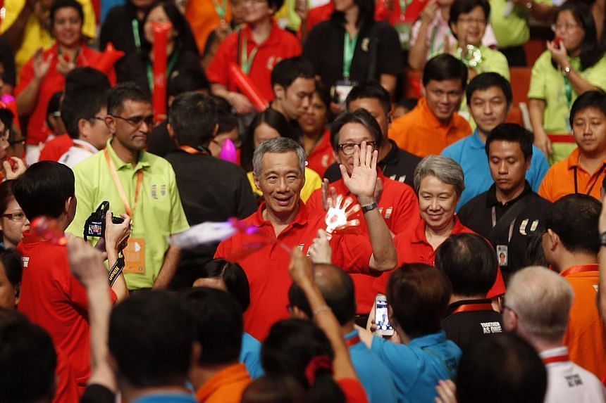 Prime Minister Lee Hsien Loong and his wife Ho Ching arrive at the National Trades Union Congress (NTUC) May Day Rally on May 1, 2015. Walking behind them are: outgoing labour chief Lim Swee Say (in red, behind Ms Ho Ching), Manpower Minister Tan Chu