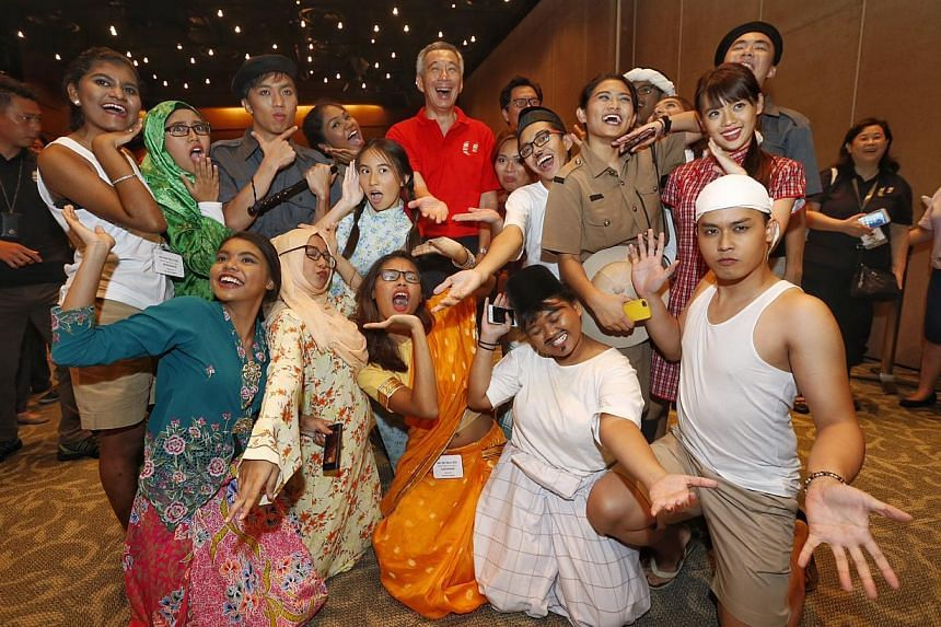 Prime Minister Lee Hsien Loong taking a group photo with performers after the May Day celebration. -- ST PHOTO: KEVIN LIM