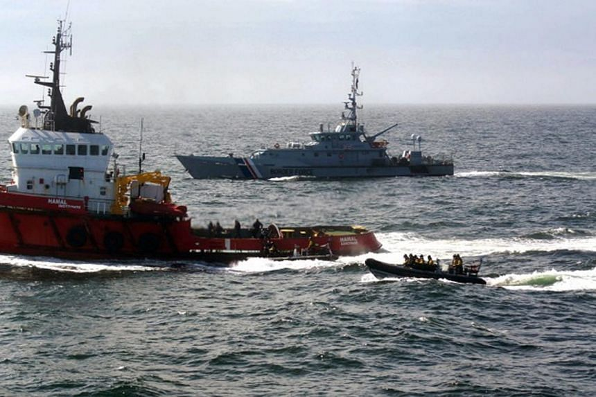 A handout photograph made available by the British National Crime Agency (NCA) on April 30, 2015, showing the MV Hamal (left) being boarded by a team from the British Royal Navy frigate HMS Somerset and Border Force cutter Valiant on April 23, 2015.