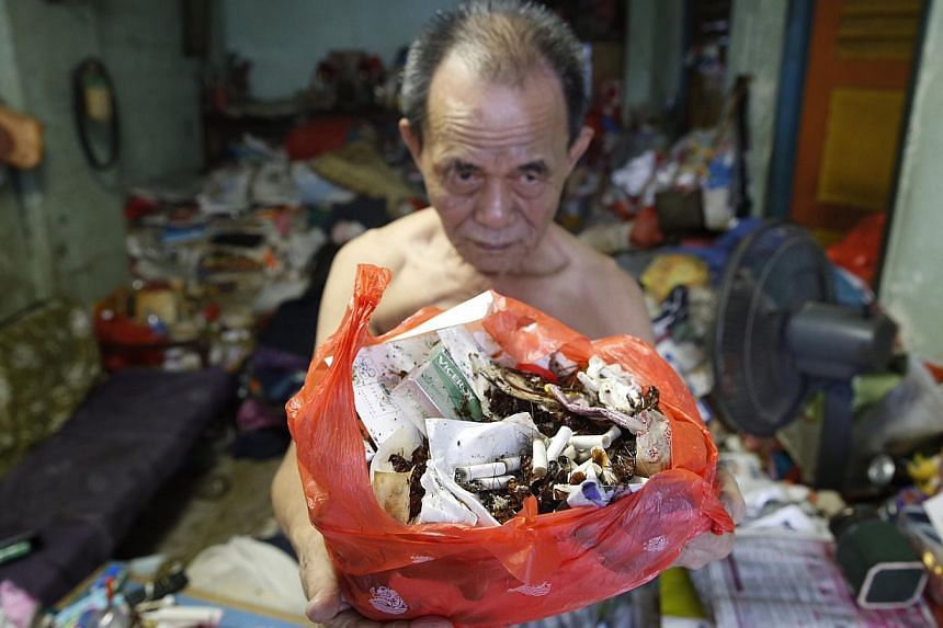 Mr Lim Chin Ting, 74, with a bag of cockroach remains and rubbish from his Eunos Crescent flat. His wife, Madam Soh Siew Zhen, has a compulsive hoarding habit, leading to a cluttered flat overrun by cockroaches and flies.