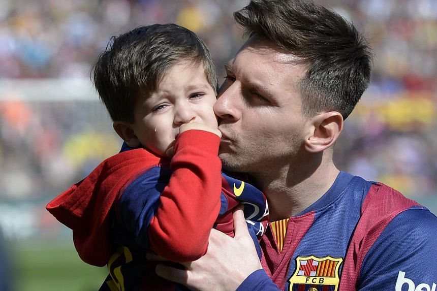 Barcelona's Argentinian forward Lionel Messi holds his son Thiago Messi before playing against Rayo Vallecano on March 8, 2015. Barcelona superstar Lionel Messi announced on Thursday he is to be a father again by posting a picture of his pregnant par