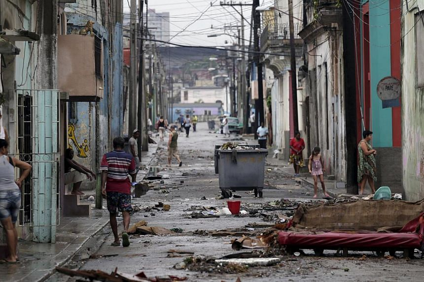 People walk on a street after flooding caused by heavy rains in Havana April 30, 2015.Three people died as a result of torrential rains and high winds that damaged more than two dozen structures and flooded parts of Havana, local media reported