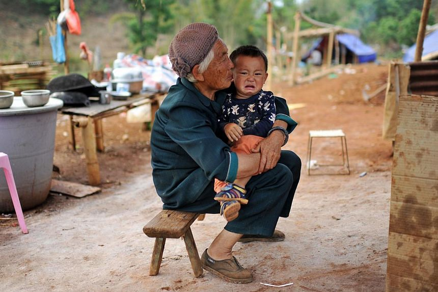 This picture taken on April 6, 2015, shows a Kokang refugee holding a child in her arms at a temporary shelter in the border area of China and Myanmar in Nansan township in Lincang, southwest China's Yunnan province. Tens of thousands of refugees hav