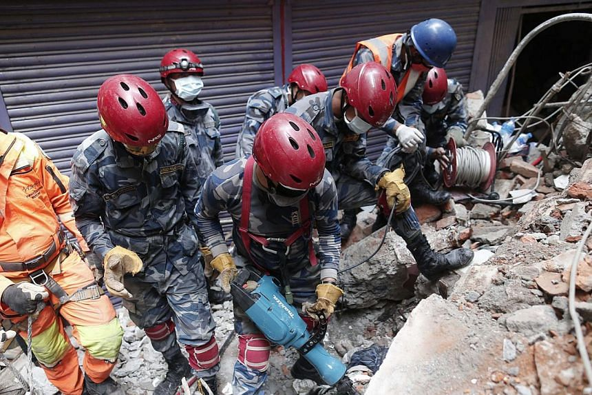 Members of a search and rescue team work in the rubble of a destroyed building in Kathmandu, Nepal, 01 May 2015. One thousand people from the European Union are missing in Nepal and 12 are confirmed dead, nearly a week after a devastating earthquake,