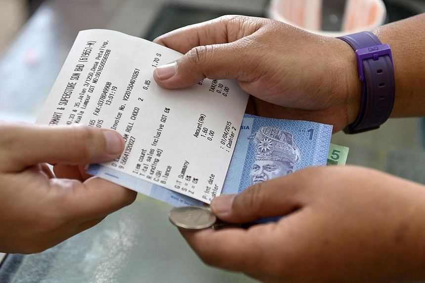 A customer receives a receipt with goods and services tax (GST) information from the cashier counter at a supermarket in Kuala Lumpur on April 1, 2015. Protesters, most of them wearing red, gathered at several areas in the vicinity of Padang Merdeka