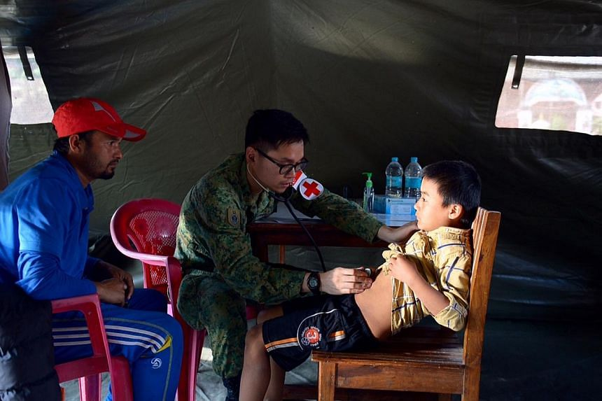 Major (Dr) Kok Wai Leong inspecting 10-year-old Pramod Rai, who complained of pains in his stomach. -- ST PHOTO: DESMOND FOO