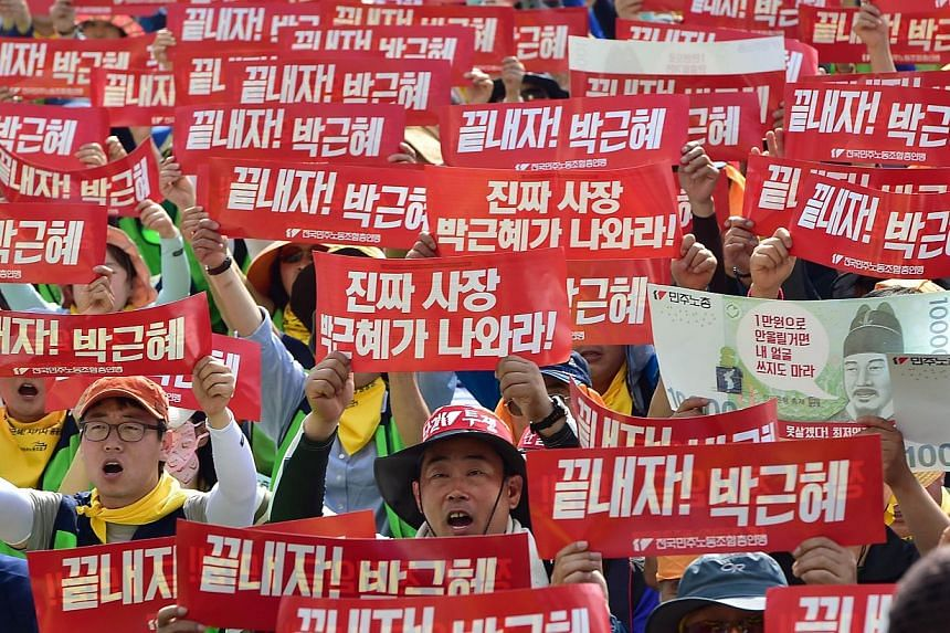 """South Korean workers shout slogans with red banners reading Let's terminate Park Geun-Hye (government) during a May Day rally in Seoul on May 1, 2015. Tens of thousands of South Korean workers rallied in Seoul, vowing to wage an """"all-out general stri"""