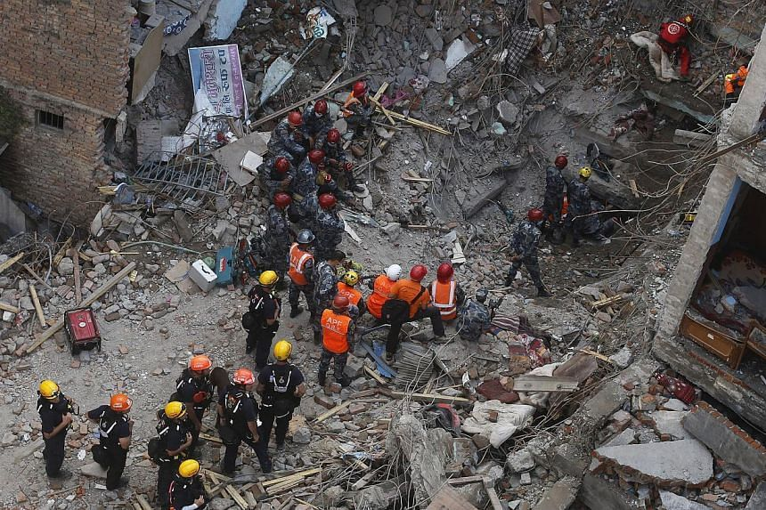 Members of a rescue team from Hungary and Nepal armed police personnel search for earthquake survivors under the debris of a collapsed building, in Kathmandu, Nepal on April 30, 2015. -- PHOTO: REUTERS