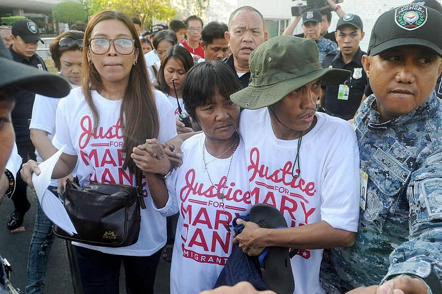 Celia Veloso (centre), the mother of Mary Jane Veloso, is escorted by a supporter upon her return from Jakarta in Manila on May 1, 2015. -- PHOTO: AFP