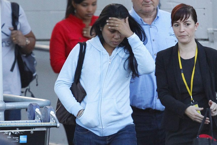 Febyanti Herewila (centre), the widow of convicted Bali Nine drug smuggler Andrew Chan, covering her face after arriving at the international airport in Sydney on May 2, 2015. -- PHOTO: EPA
