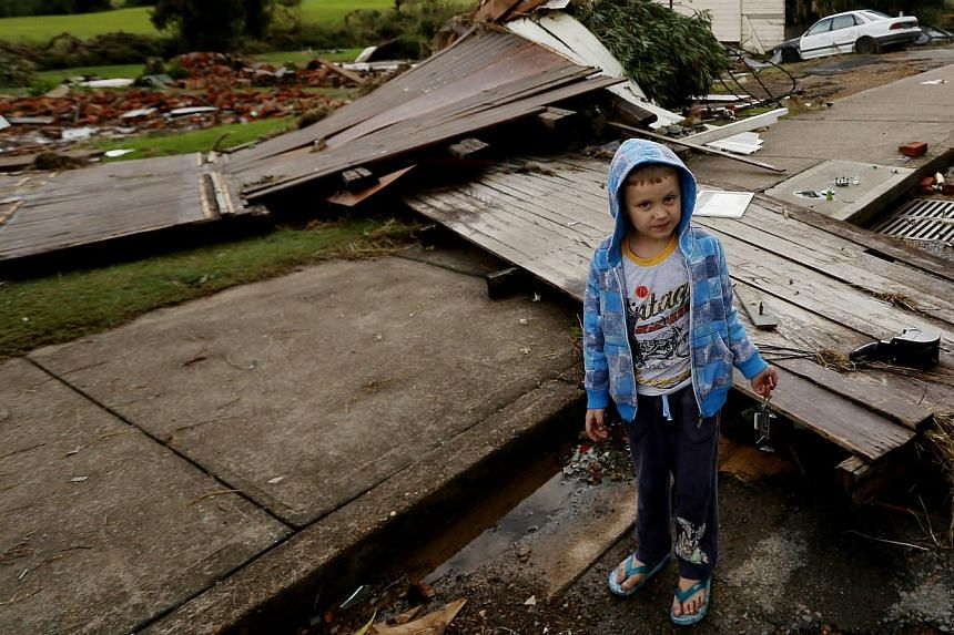 A young child amongst the damage and destruction caused by flooding in Dungog in the New South Wales, Hunter region, Australia on April 22, 2015. --PHOTO: EPA