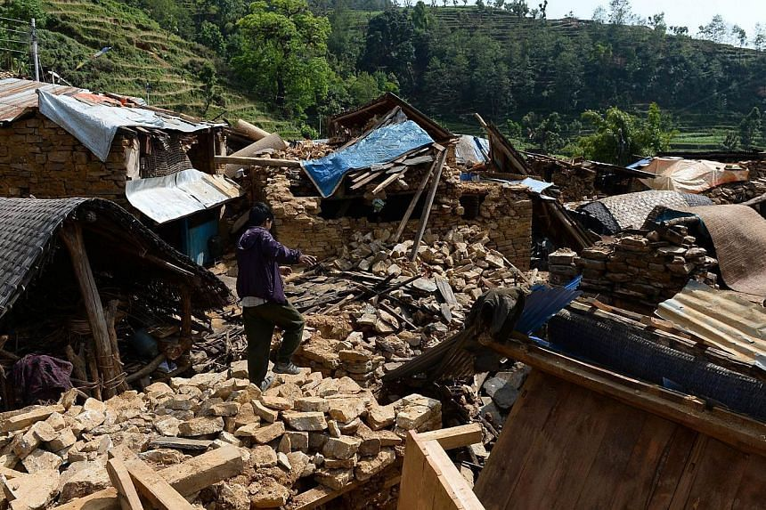 A Nepalese villager walks on the rubble of damaged homes in Baluwa, Gorkha District on May 1, 2015, following a 7.8 magnitude earthquake which struck the Himalayan nation on April 25, 2015. -- PHOTO: AFP