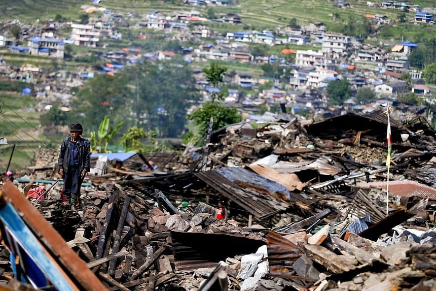 A man standing on what is left of his village as residents return to their dilapidated homes to salvage what they can in Barpak village at the epicentre of the devastating earthquake that hit the country in Nepal on May 1, 2015. -- PHOTO: EPA