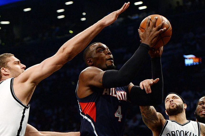 Atlanta Hawks' Paul Millsap (centre) drives to the basket past the Nets' Brook Lopez (left) and Deron Williams (right) during the first half of game six of the NBA playoff match at the Barclays Centre in Brooklyn, New York on May 1 2015. -- PHOT