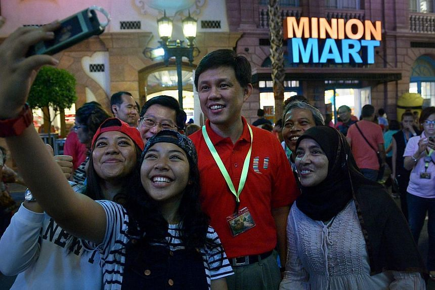 NTUC's Deputy Secretary-General Chan Chun Sing posing with members of the public at Universal Studios Singapore on May 2, 2015. -- ST PHOTO: KHUA CHEE SIONG