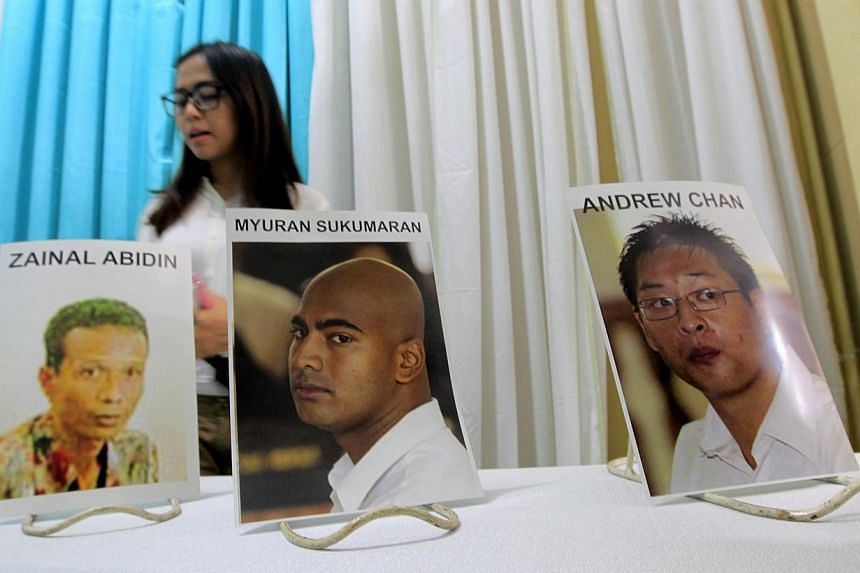 An Indonesian girl walks past pictures of executed Australian death-row prisoners Andrew Chan (right) and Myuran Sukumaran (centre), and Indonesian Zainal Abidin, at the Saint Carolus funeral home in Jakarta on April 29, 2015. -- PHOTO: EPA