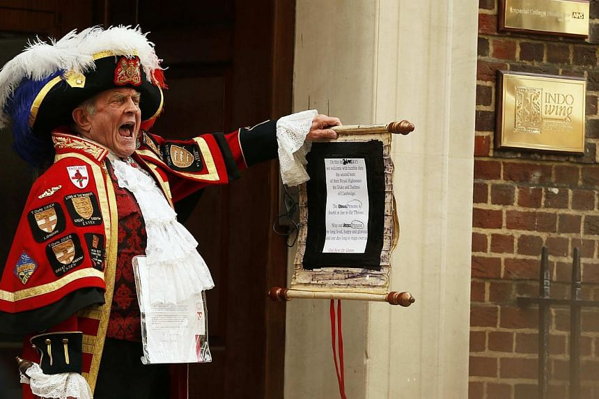 A ceremonial town crier holds a scroll after announcing the birth of a baby girl to royal fans and members of the media outside the entrance to the Lindo wing of St Mary's Hospital in London, Britain onMay 2, 2015. The birth of Britain's royal