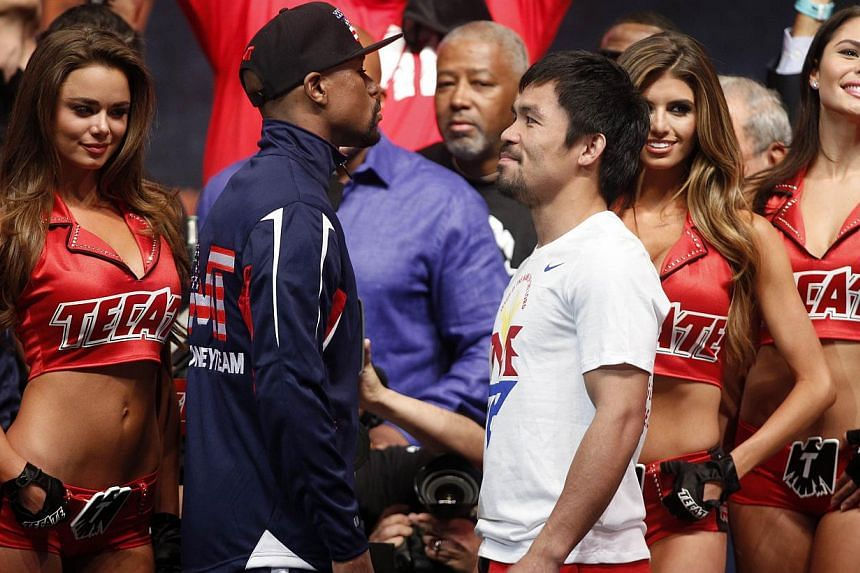 "Floyd Mayweather (centre, left) and Manny Pacquiao (centre, right) facing off following their weigh-in on May 1, 2015, in Las Vegas one day before their ""Fight of the Century"" on May 2 at the MGM Grand Garden Arena. -- PHOTO: AFP"